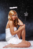 Beautiful angel girl with glory and magic stick Stock Photography