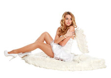 Beautiful angel girl sitting on a white carpe Stock Photography