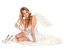 Beautiful angel girl sitting on a white carpet Stock Image