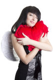 Beautiful angel woman embracing red heart Stock Image