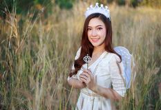 Angel woman in a grass field with sunlight Stock Photo
