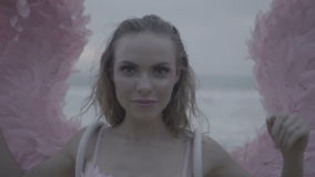 Beautiful angel woman with pink wings. Romantic young beauty as an angel on the beach. Closeup of blonde pretty female woman wearing pink wings and feather bra stock video footage