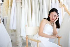 Beautiful angry and agressive shouting bride wearing white dress, screaming and crying at someone stock photo
