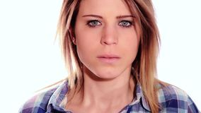 Beautiful angry girl. Portrait of an angry nice girl looking at camera over white background stock video footage