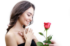 Beautiful angry girl receives one red rose. She is surprised, looking at the flowers and smiling. Royalty Free Stock Photo