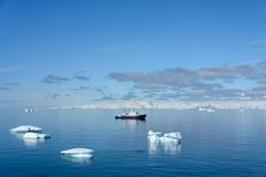 Beautiful Antarctiс seascape with iceberg and expedition ship. Beautiful Antarctiс seascape with iceberg at sea with calm weather royalty free stock images