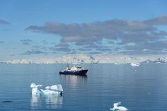 Beautiful Antarctiс seascape with iceberg and expedition ship. Beautiful Antarctiс seascape with iceberg at sea with calm weather stock image