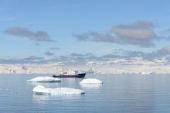 Beautiful Antarctiс seascape with iceberg and expedition ship. Beautiful Antarctiс seascape with iceberg at sea with calm weather stock photography
