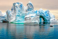 Iceberg in Antarctica, ice castle with Zodiac in front. Huge iceberg sculptured like fairytale castle
