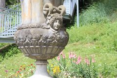 Beautiful antic vase with women face in garden stock image