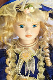 Beautiful antique doll. Old antique vintage doll with blonde spiral curls, blue eyes, big eyelashes royalty free stock image