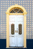 Beautiful antique door in a decorated facade Stock Images