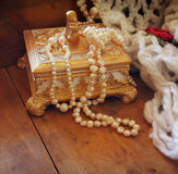 A beautiful antique golden jewelry box with natural white pearls on wooden table Royalty Free Stock Photos