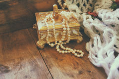 A beautiful antique golden jewelry box with natural white pearls on wooden table Stock Image