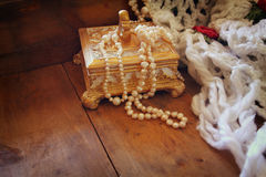 A beautiful antique golden jewelry box with natural white pearls on wooden table Royalty Free Stock Image
