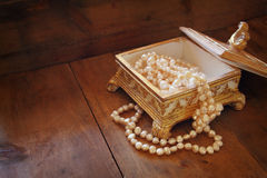 A beautiful antique golden jewelry box with natural white pearls on wooden table. retro filtered image Stock Image