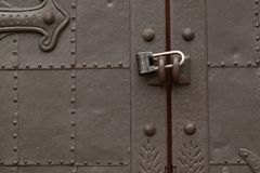 Antique metal strong door with a lock. Beautiful antique metal door with padlock, very sturdy and reliable stock images