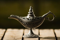 Beautiful antique metal lamp in true Aladin style, sitting on wooden surface Stock Photos