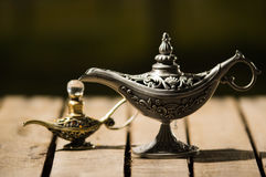 Beautiful antique metal lamp in true Aladin style, smaller model placed next to it, sitting on wooden surface Royalty Free Stock Photography