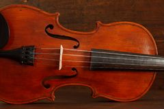 Beautiful antique violin on brown wood background stock image