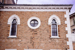 Beautiful antique windows with friezes on a brick building Stock Images