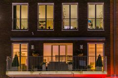 Beautiful apartment balcony decorated with plants, lighted windows by night, Modern dutch architecture royalty free stock photography