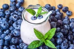 Beautiful appetizer blueberry fruit smoothie milk shake glass jar with juicy fresh berries background top view Yogurt cocktail Nat. Beautiful appetizer blueberry Royalty Free Stock Photo