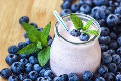Beautiful appetizer blueberry fruit smoothie milk shake glass jar with juicy fresh berries background top view Yogurt cocktail Nat. Beautiful appetizer blueberry Royalty Free Stock Photos
