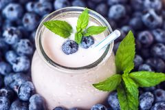 Beautiful appetizer blueberry fruit smoothie milk shake glass jar with juicy fresh berries background top view Yogurt cocktail Nat. Beautiful appetizer blueberry Royalty Free Stock Photography