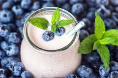 Beautiful appetizer blueberry fruit smoothie milk shake glass jar with juicy fresh berries background top view Yogurt cocktail Nat. Beautiful appetizer blueberry Stock Image