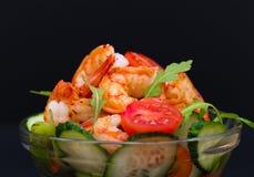 Food. Langoustines salad, black background. Beautiful appetizer langoustines salad, decorated vegetables cucumber and rukola.  Black background. Close up. Fried Royalty Free Stock Photography