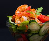 Food. Langoustines salad, black background. Beautiful appetizer langoustines salad, decorated vegetables cucumber and rukola.  Black background. Close up. Fried Royalty Free Stock Photos