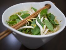 Beautiful and appetizing photo of a traditional vietnamese chicken noodle soup, also know as Pho Ga. In a white bowl with wooden b. Ackground and luxurious royalty free stock image