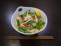 Beautiful and appetizing photo of a traditional vietnamese chicken noodle soup, also know as Pho Ga. In a white bowl with wooden b. Ackground and luxurious royalty free stock photos