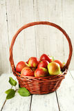 Beautiful apples in basket on white wooden background Stock Images