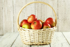 Beautiful apples in basket on white wooden background Royalty Free Stock Photography