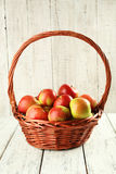 Beautiful apples in basket on white wooden background. Royalty Free Stock Photos