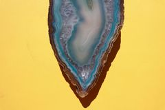 Aqua Blue Crystal Agate Stone on Bright Yellow Background royalty free stock images