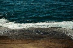 Beautiful aquamarine sea waves crash against brown stones Stock Photos