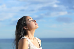Beautiful arab woman breathing fresh air in the beach. With a cloudy blue sky in the background Stock Photos