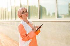 Beautiful arabian girl with tablet computer. Muslim woman. Stock Photos