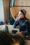 Beautiful Arabic Muslim girl using tablet in cafe. Portrait of beautiful Arabic Muslim girl using tablet in cafe Stock Photography