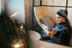 Beautiful Arabic Muslim girl using tablet in cafe. Portrait of beautiful Arabic Muslim girl using tablet in cafe Royalty Free Stock Photos
