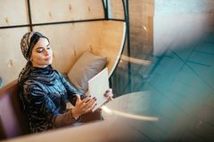 Beautiful Arabic Muslim girl using tablet in cafe. Portrait of beautiful Arabic Muslim girl using tablet in cafe Stock Image