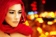 Beautiful arabic woman. Wearing red scarf, stylish female face portrait over night city,  blur lights abstract  background, serious expression, stunning sensual Royalty Free Stock Image
