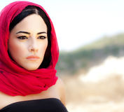 Beautiful arabic woman. Wearing red scarf, traditional muslim clothes, stylish female portrait over soft natural background with copy space Stock Photography