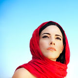 Beautiful arabic woman. Wearing red scarf, traditional muslim clothes, latest fashion design, stylish female portrait over blue natural background with copy Stock Photo