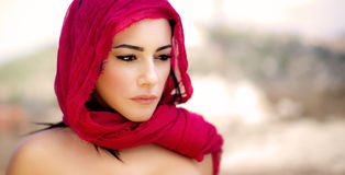 Beautiful arabic woman. Wearing red scarf, stylish female portrait over soft natural background with copy space Royalty Free Stock Photos