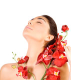 Beautiful woman with red orchid flowers. Beautiful arabic woman with closed eyes and red orchid flowers isolated on white background, enjoying dayspa, beauty Royalty Free Stock Photography