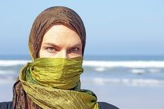 Beautiful arabic woman at the ocean. Beautiful arabic woman with green scarf at the ocean Royalty Free Stock Photo